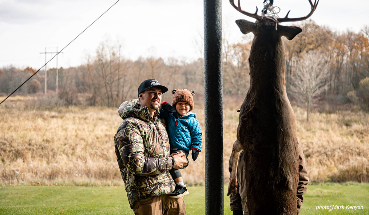 Mark Kenyon with his son looking at a whitetail deer shot while hunting in Michigan.