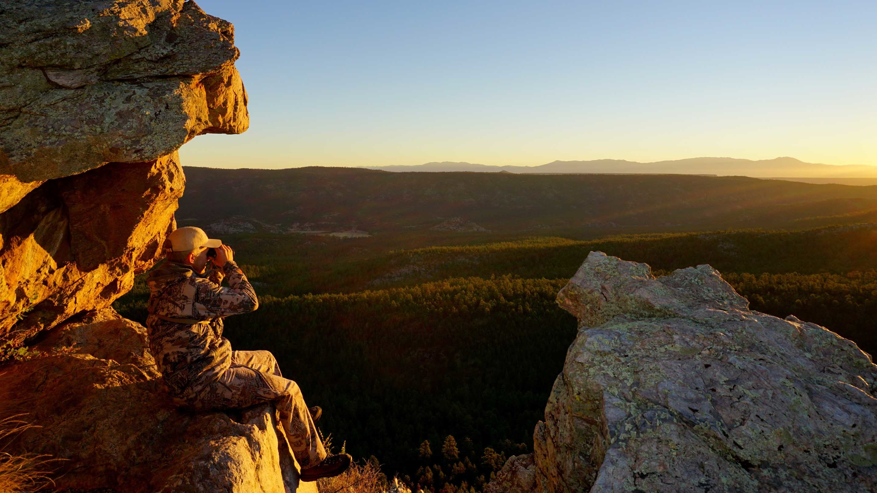 Image of hunter watching the sunset from a rocky mountainside in public lands.