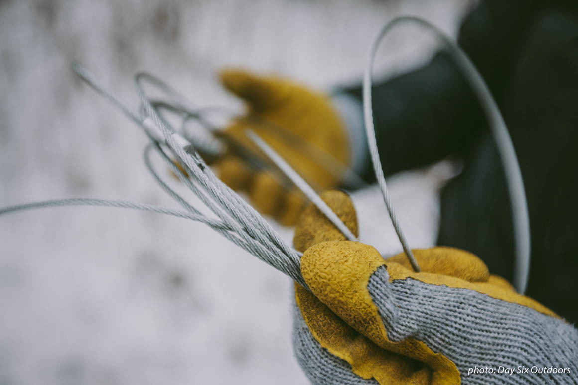 Man setting up snare trap in the winter, wearing gloves in the snow, for animal trapping.