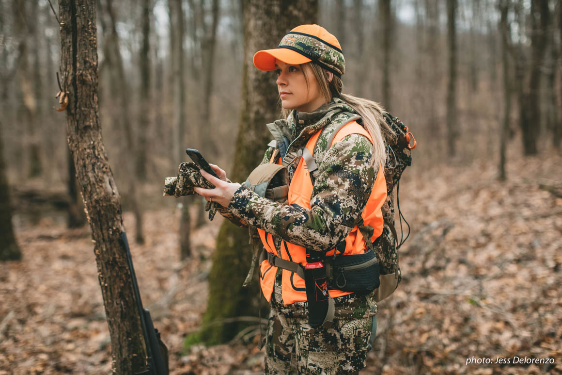 Woman hunting in woods in camouflage with cell phone.