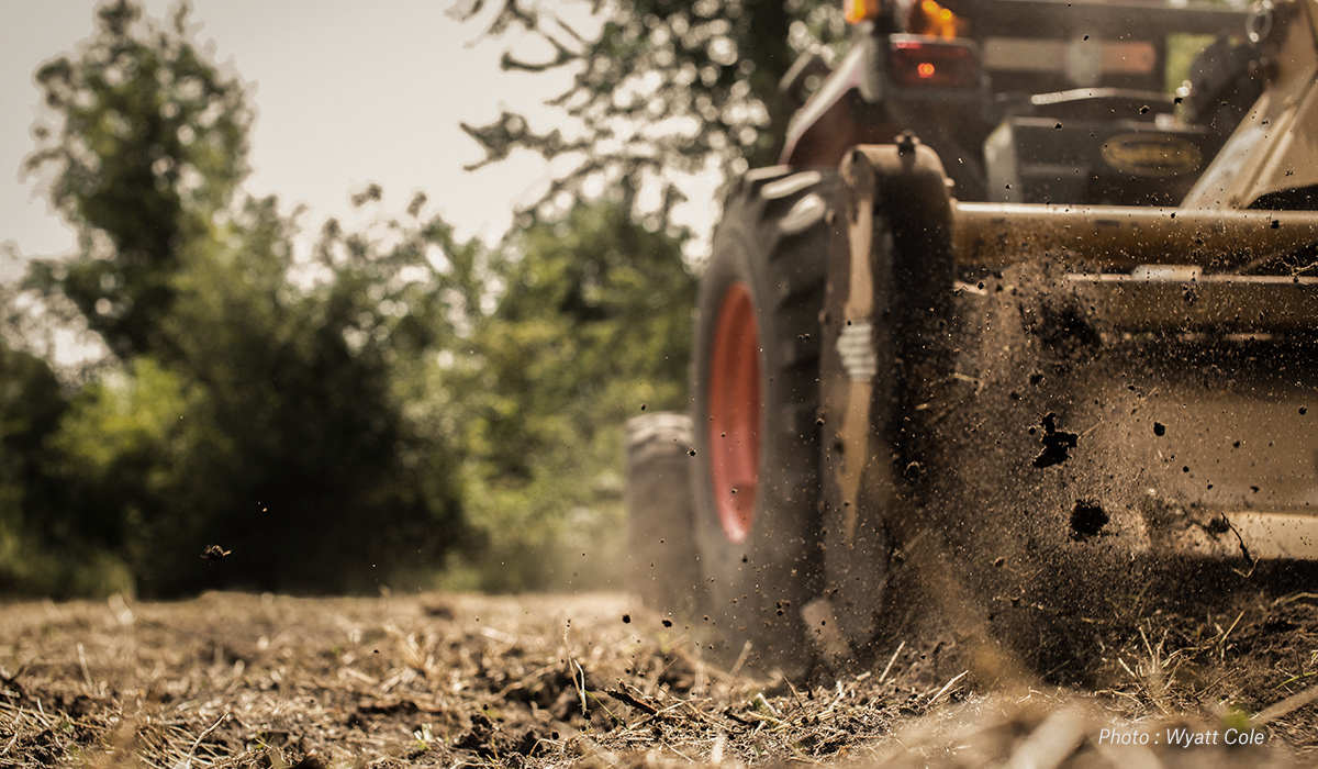 A tractor breaks ground.