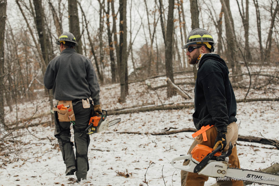 Two men with chainsaws work in snowy woods.