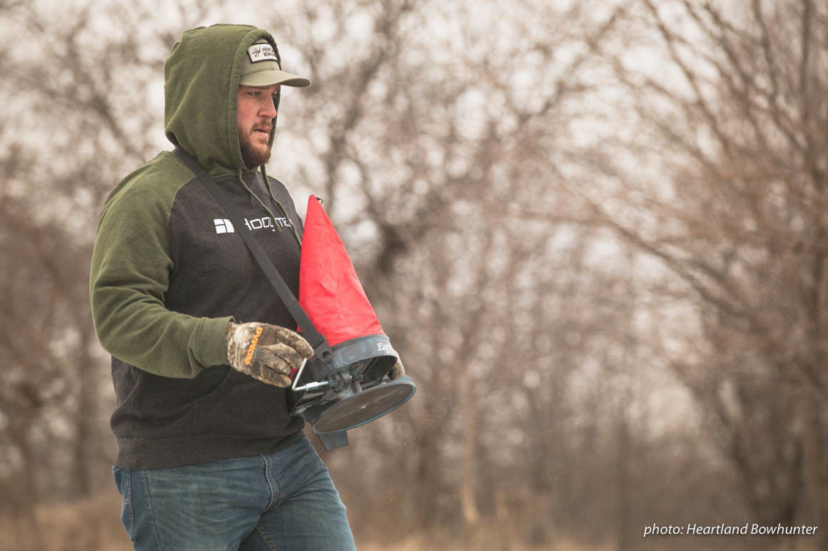 Man walking and distributing seed in a field in the winter.