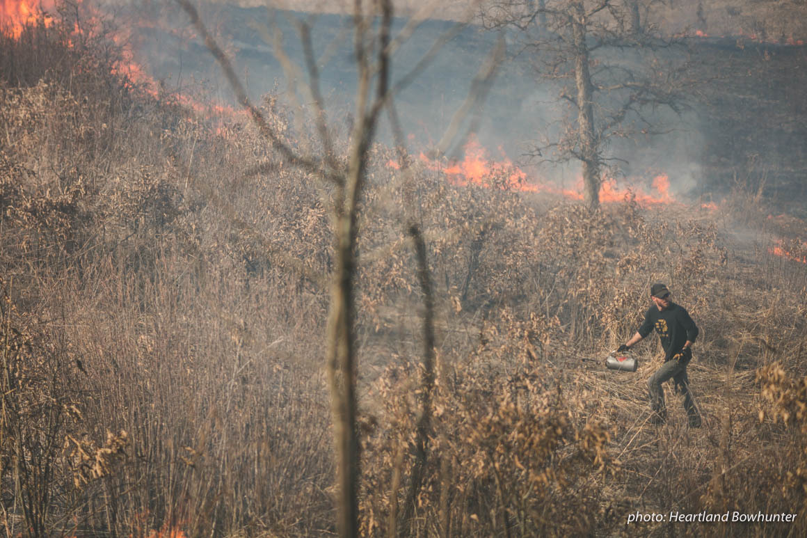 Man in field doing controlled burn to halp manage land for hunting.