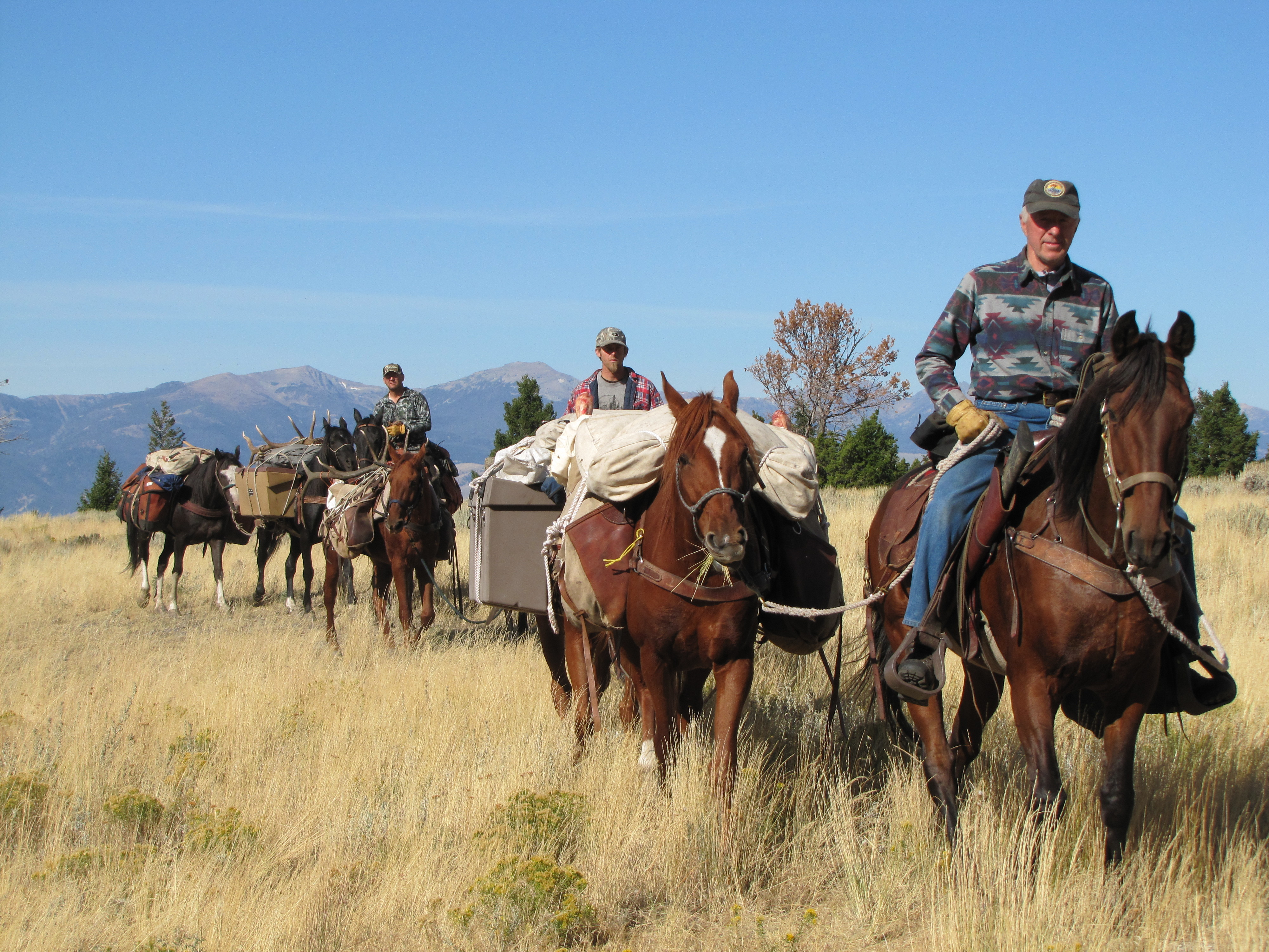 George Bettas on horseback leading a pack train.