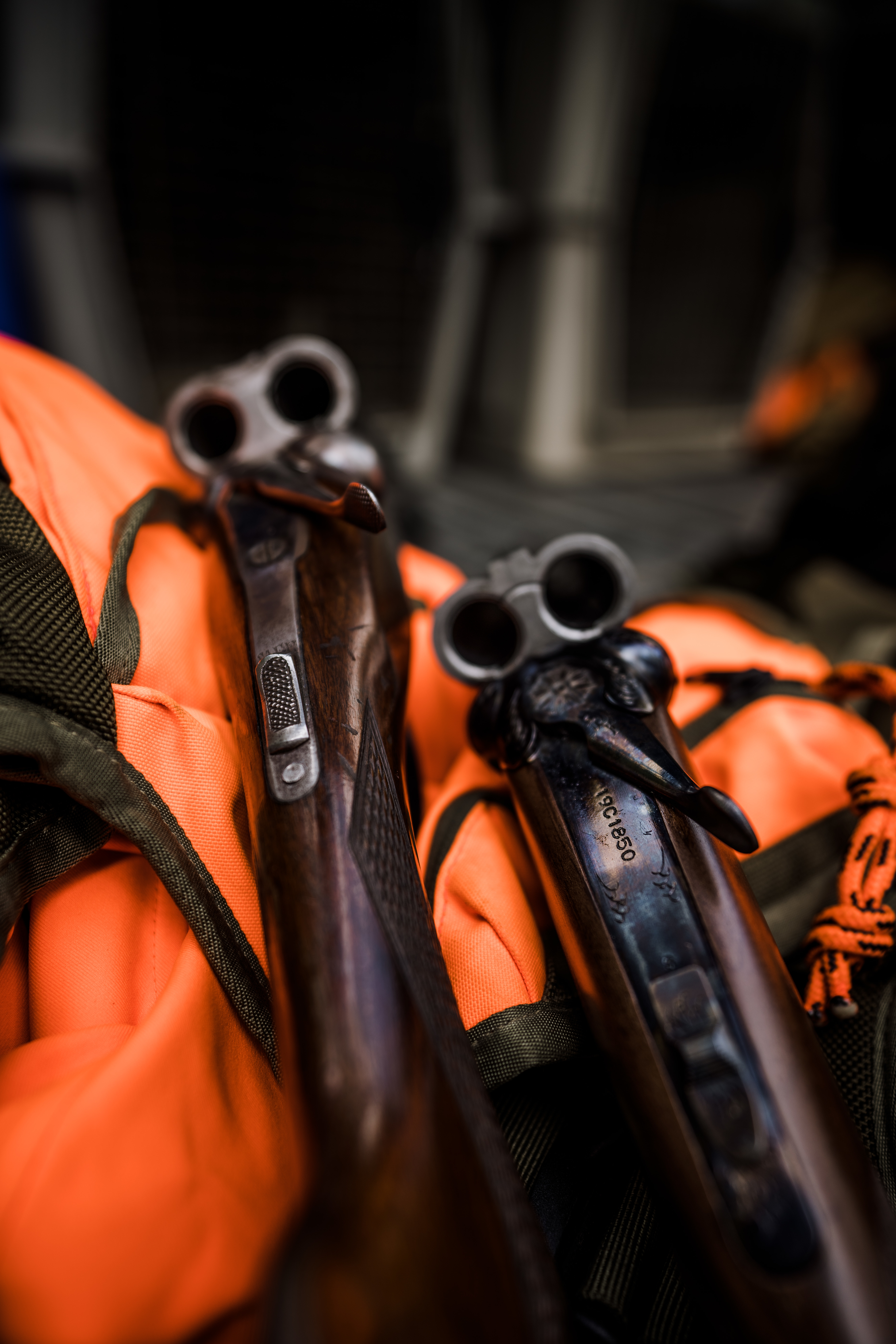 Two side-by-side shotguns rest on an orange upland vest.