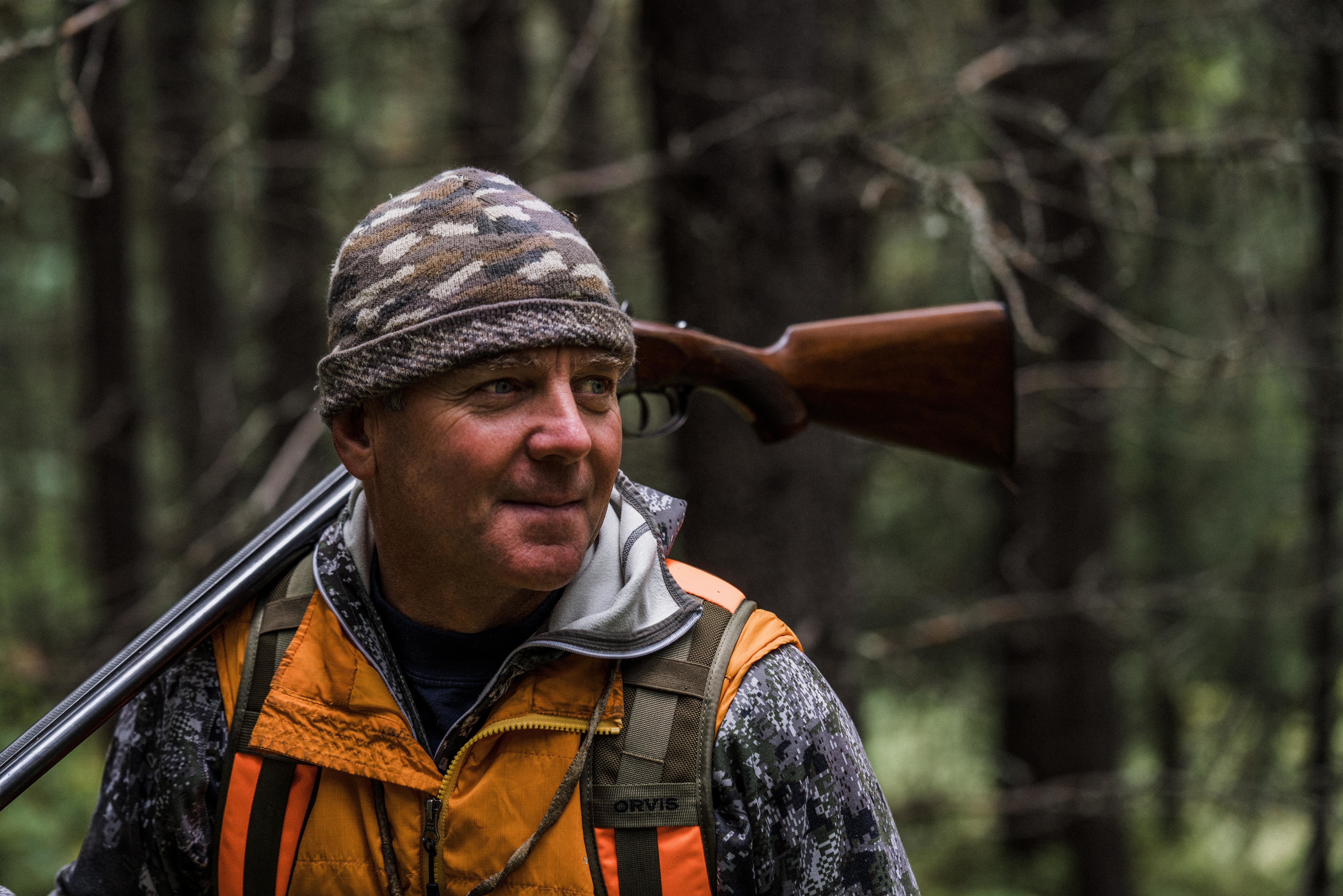 Montana outfitter Tim Linehan carries a shotgun while grouse hunting.