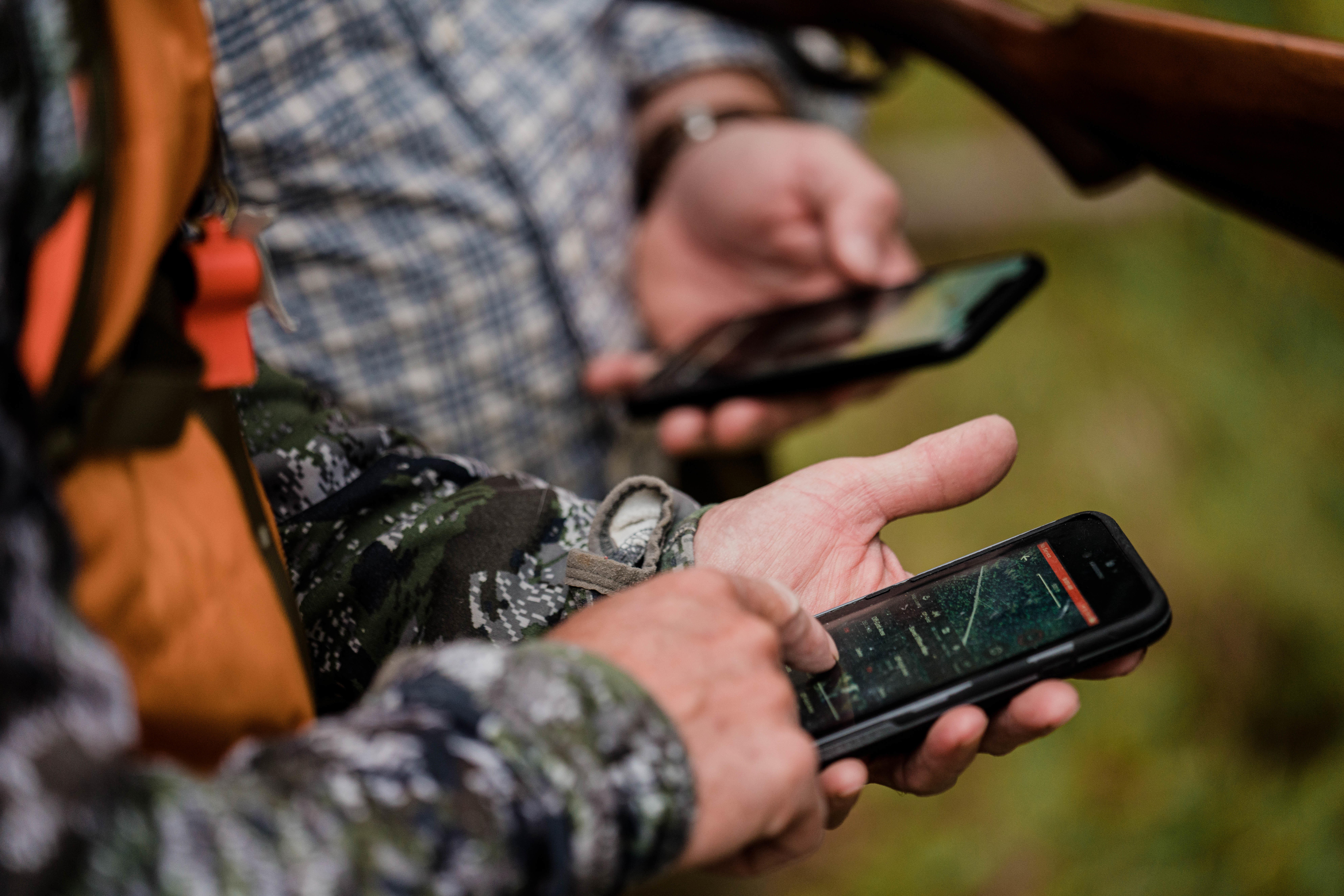 Two hunters use the onX Hunt App to decide which direction to go.