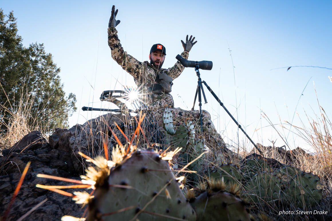 Hunter in camo excited while looking through scope, hunting in Arizona for mule deer.