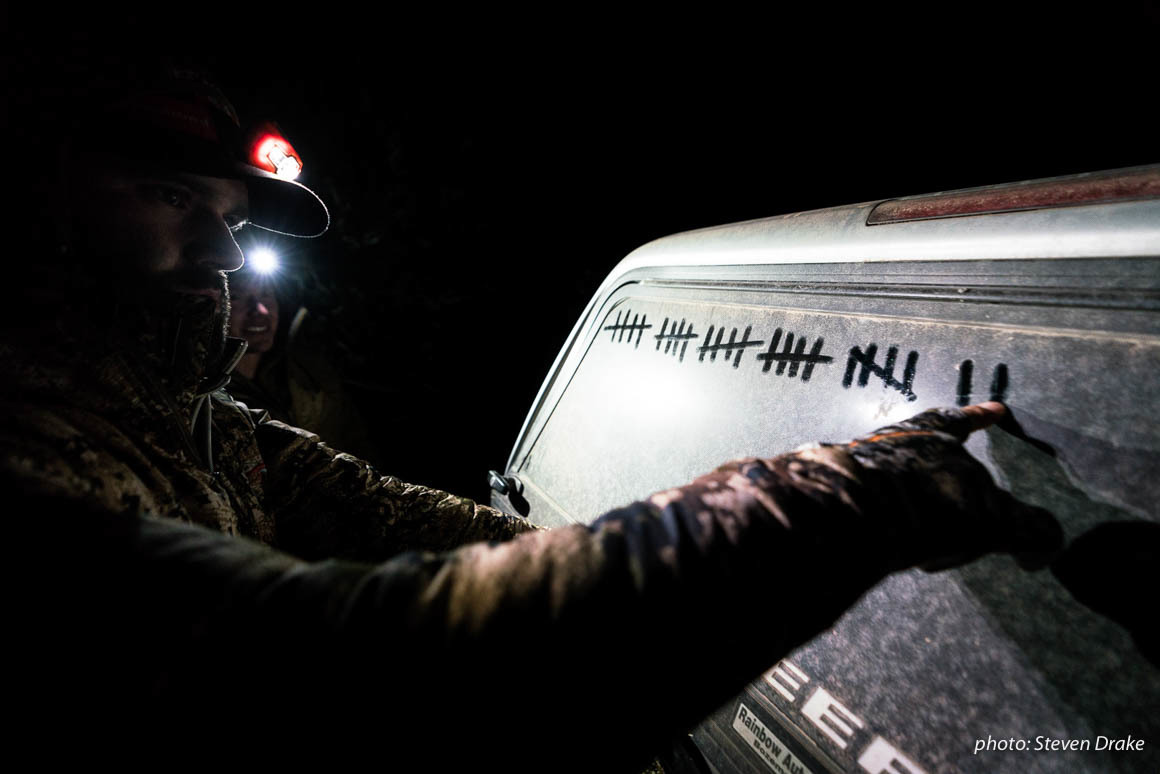 Hunter marking hash marks on the back of a dirty truck while hunting in Arizona.