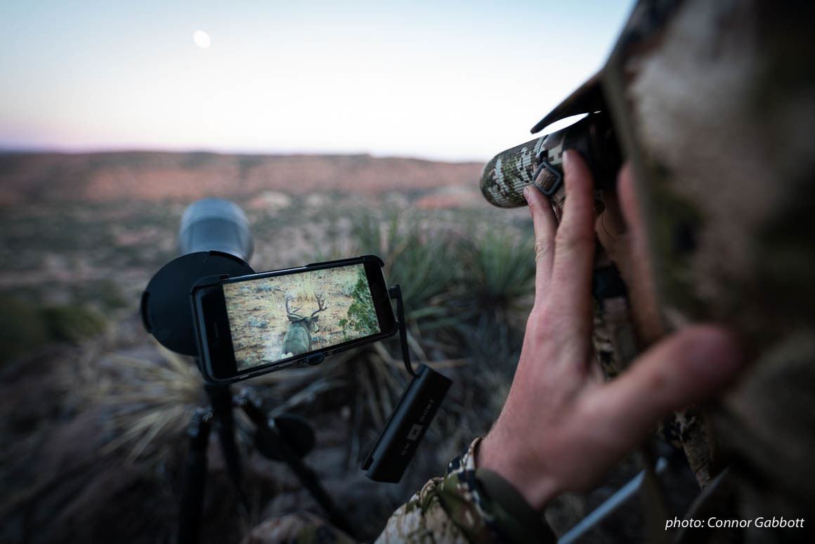 Man watches deer through phone scope while hunting in Arizona.