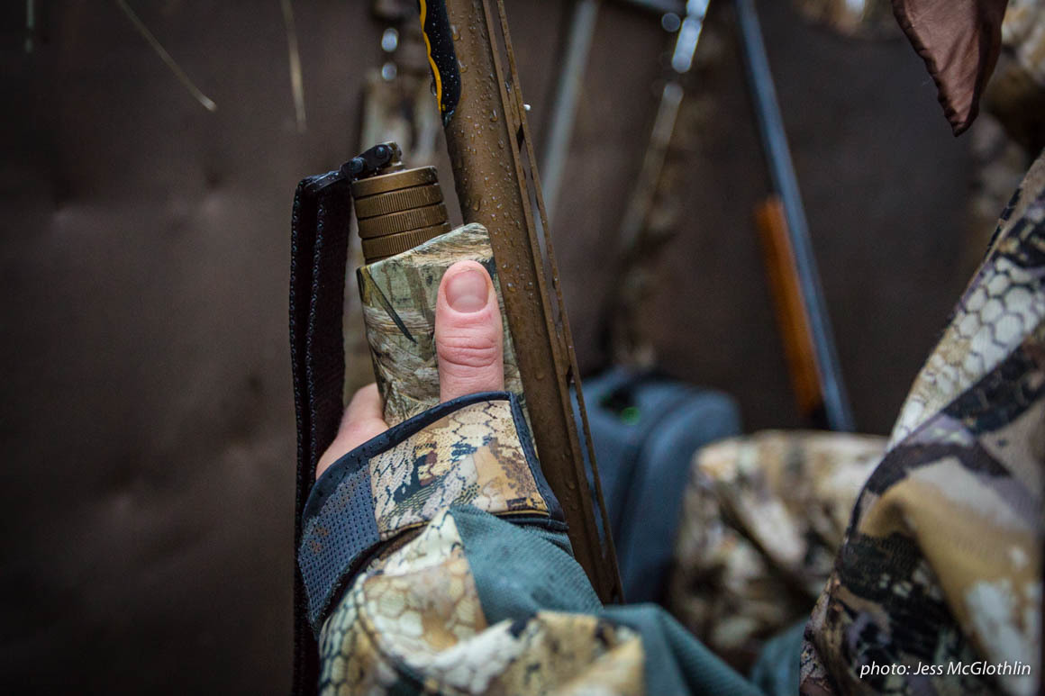 Hand of a waterfowl hunter holding a shotgun while in a goose blind.