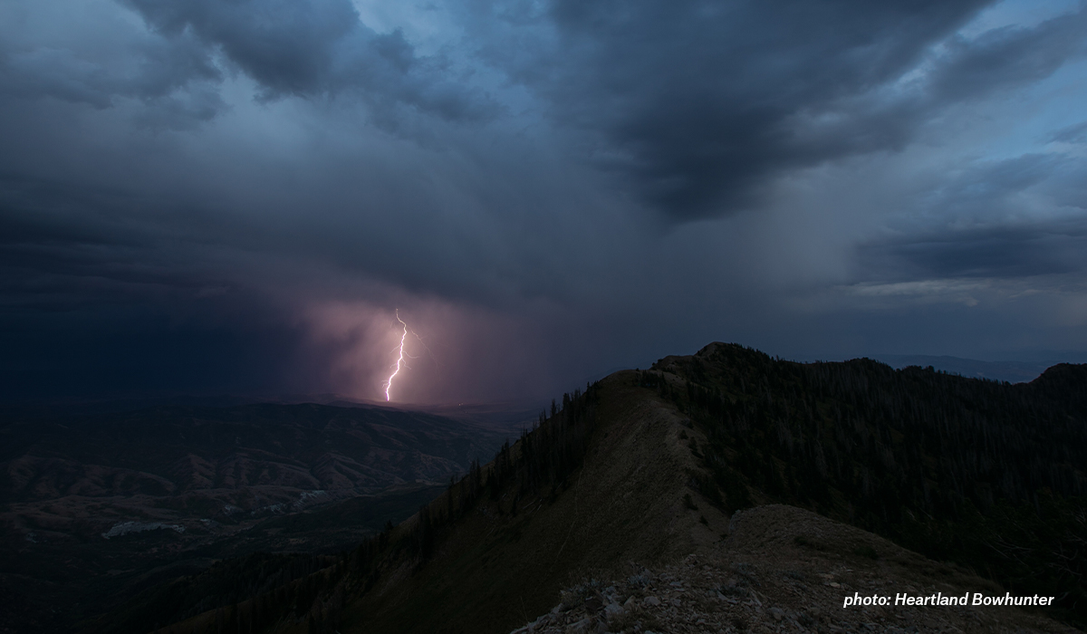Lightning striking mountain during thunderstorm.