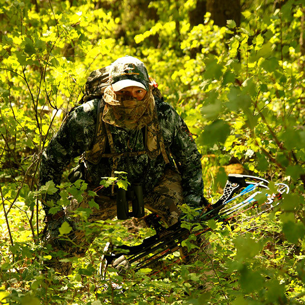 Image of hunter in full camouflage sneaking through the woods with bow in hand.