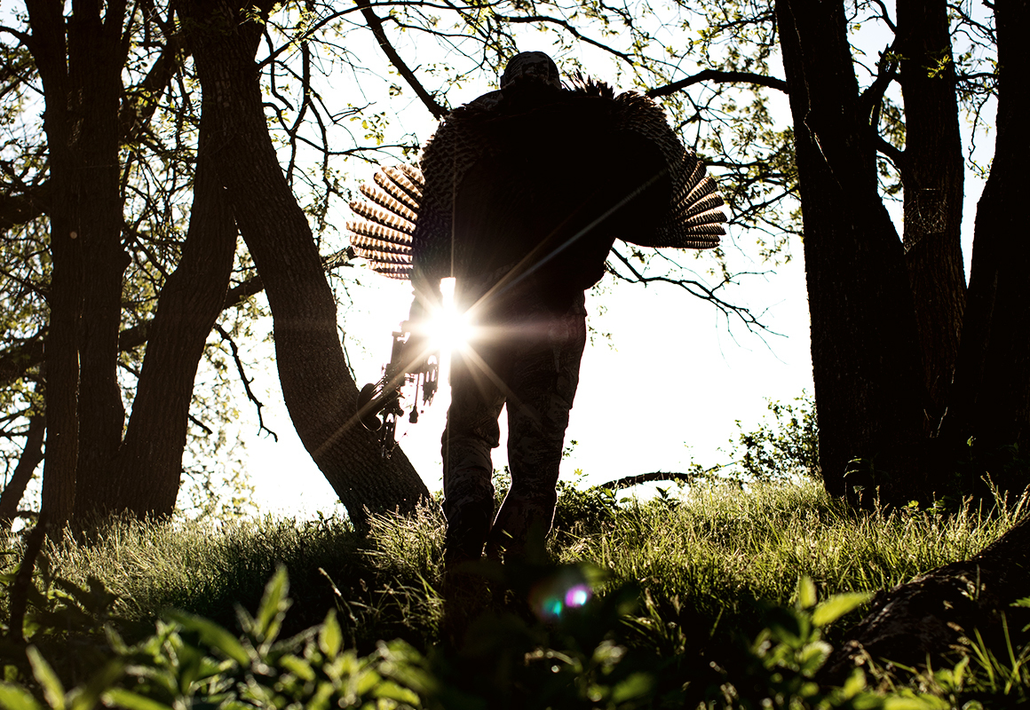 Image of man silhouetted against the sky, walking up a hill with a turkey over his shoulder.