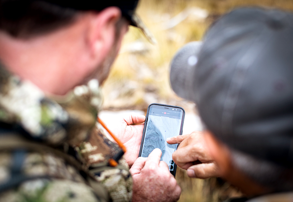 Two men look at a phone displaying the onX Hunt App while scouting in the woods and hunting.