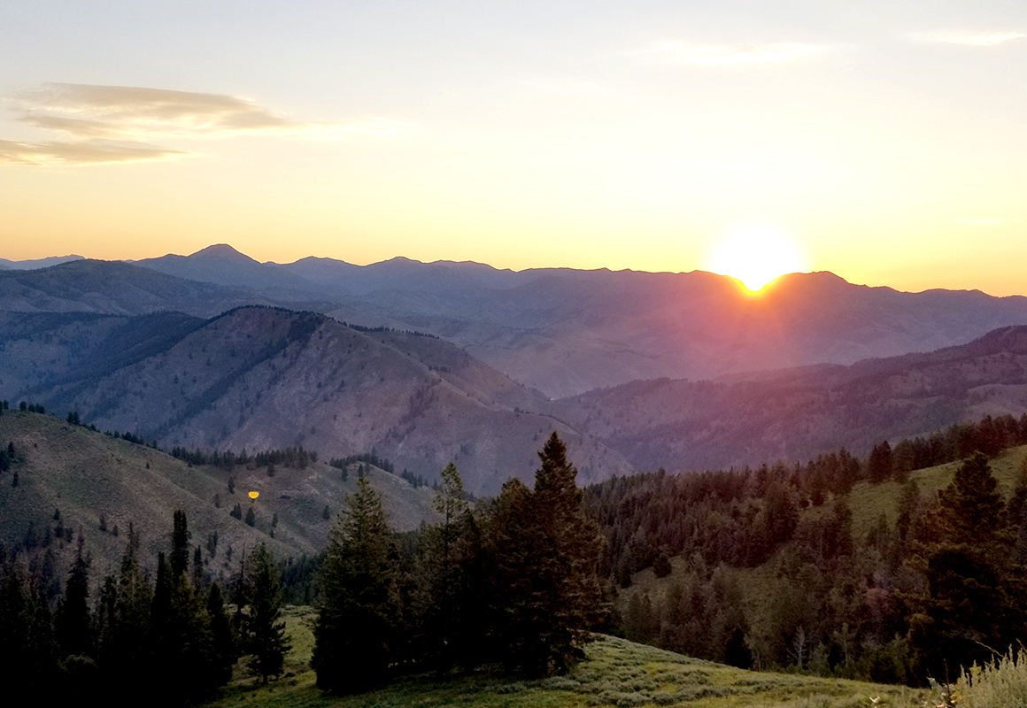 A wilderness sunset in the mountains, as the sun sets below the horizon.