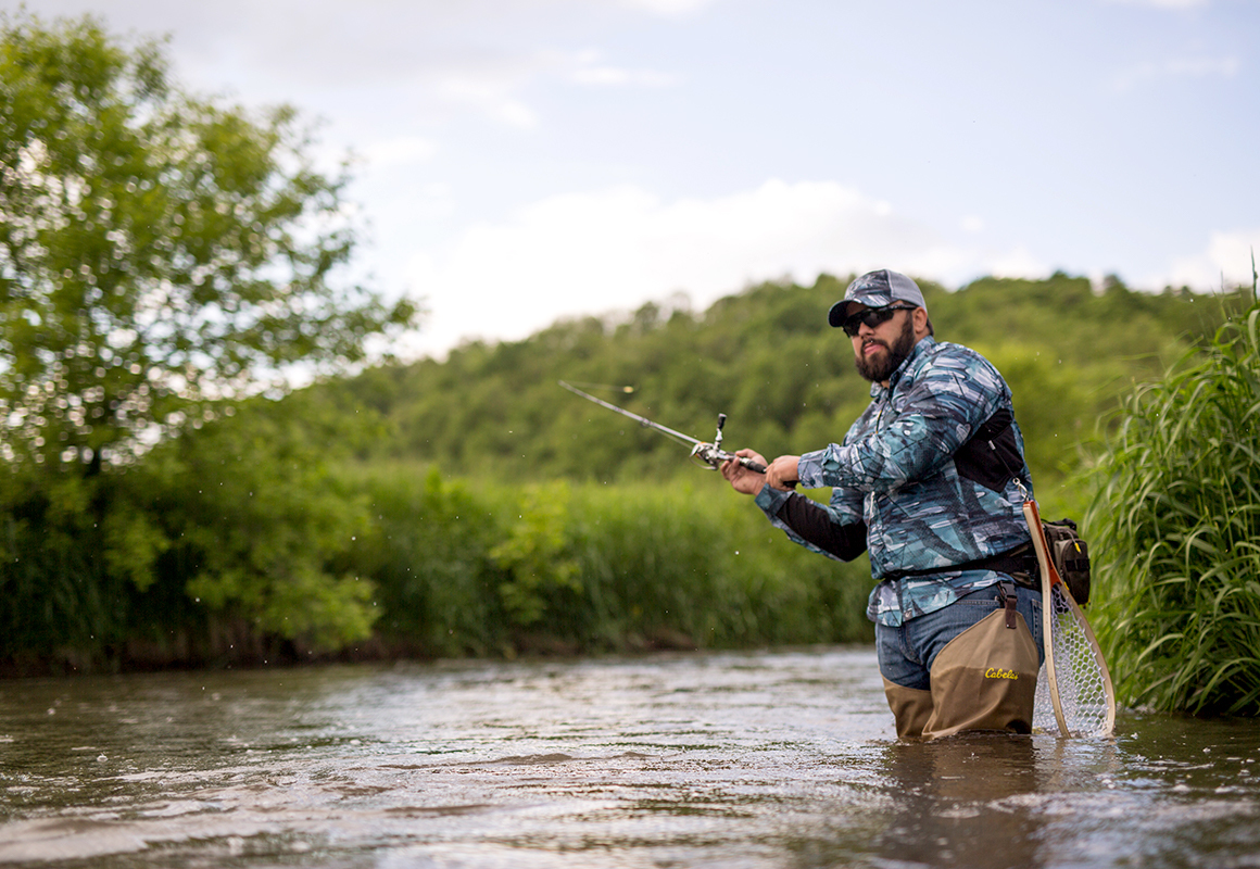 Fly fisherman using the onX Hunt app for finding river access