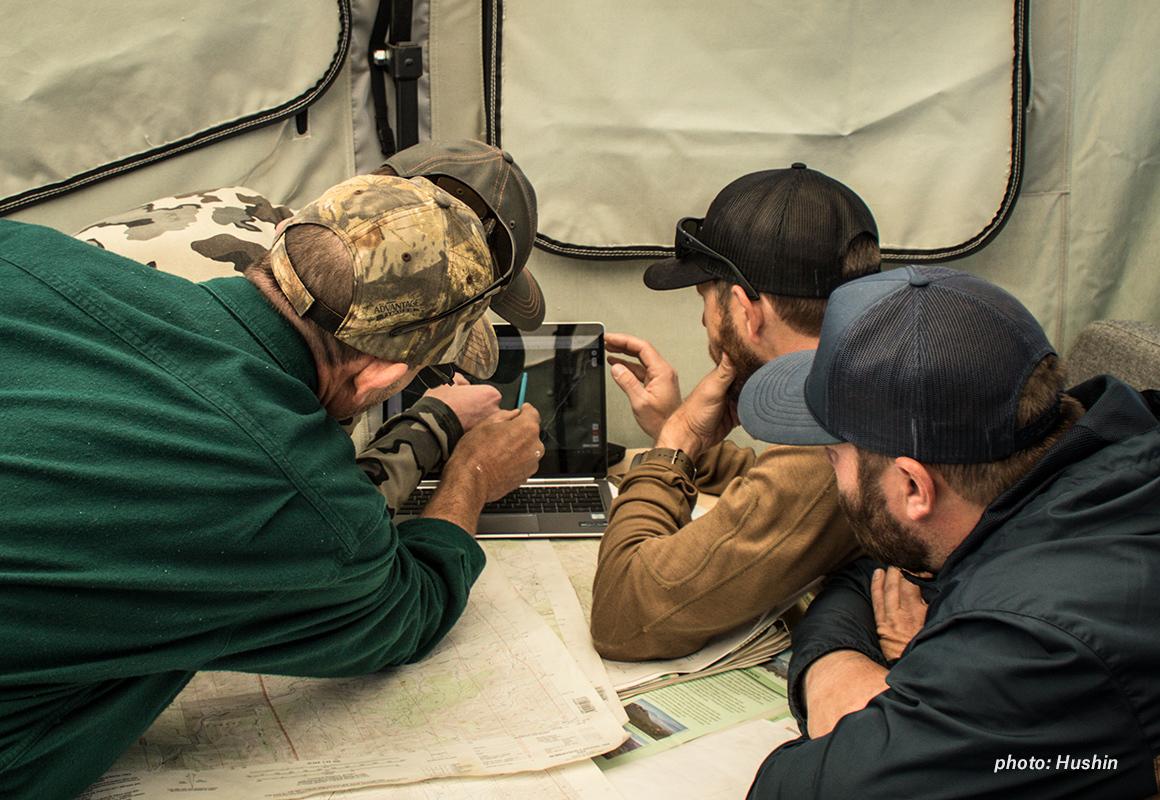 Men gathered in a tent around a computer, e-scouting on onX Hunt Web Map before they go hunting.